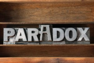 das Wort Paradox in Metallbuchstaben auf einem Regal