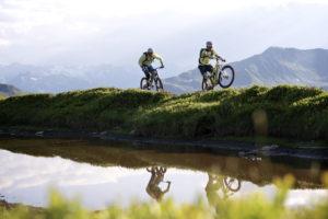 zwei Montainbiker spiegeln sich auf einem Hügel im darunter befindlichen Wasser