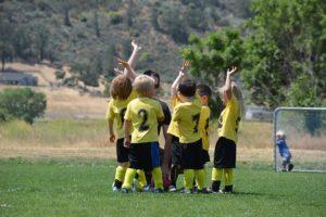 kleine Kinder in Trikots auf dem Fußballplatz erheben die Hände