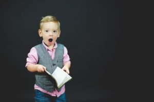 kleiner Junge hält mit offenem Mund ein Buch in der Hand