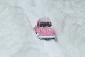 Rosa VW Käfer zwischen auftürmendem Schnee
