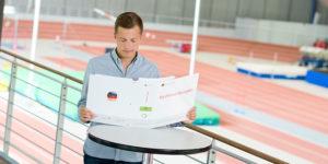 junger Mann vor einem Sportplatz studiert ein Papier