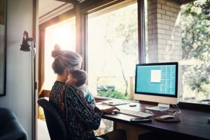 Frau mit Baby auf dem Arm vor dem Rechner