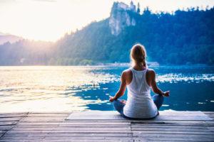 junge Frau im Yogasitz vor einem See