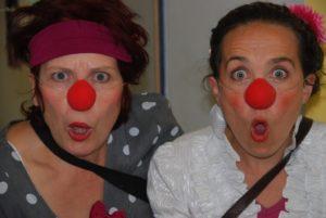 zwei Clowns mit roten Nasen und erstaunten Gesichtern