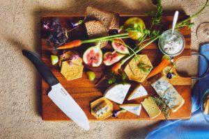 Brett mit Speisen und Küchenmesser