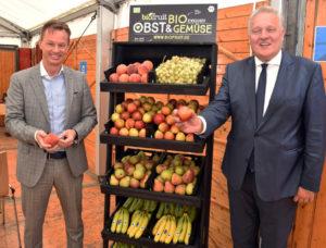 Zwei Männer neben einem Fruchtregal