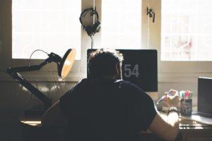 junger Mann von hinten an seinem Schreibtisch