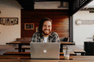Lächelnder Mann vor einem Laptop im Café