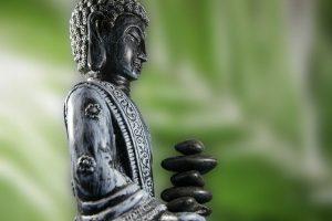 eine Buddha-Statue vor grünem Hintergrund