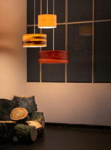 drei stylische Lampen vor einem Exponat an der Wand