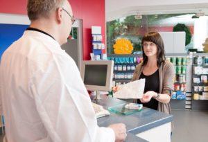Junge Frau zeigt einem Apotheker einen Beipackzettel