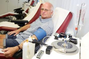 Mann liegt auf einer Liege, angeschlossen an eine Blutzentrifuge