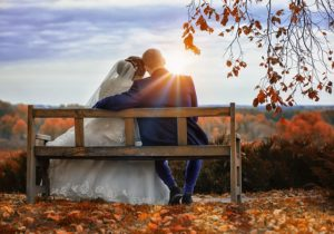 Hochzeitspaar auf einer Bank blickt auf den Sonnenuntergang
