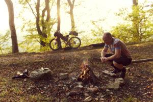 mann hockt im Wald vor einem Lagerfeuer