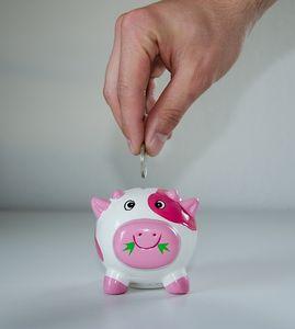 eine Hand wirft eine Münze in ein Sparschwein