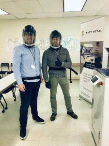 Zwei Männer mir Helmen vor dem Drucker