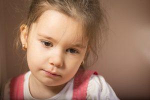 ein kleines Mädchen sieht in sich zurückgezogen aus
