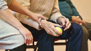 eine Hand hält die Hand eines älteren Menschen
