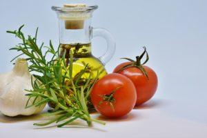 Olivenöl mit Rosmarinzweig, Knoblauch und Tomaten