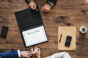Heiratsurkunde auf einem Holztisch von oben betrachtet