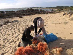 Menschen entwirren ein Fischernetz