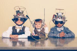 Kinder sitzen mit Helmen verdrahtet am Tisch