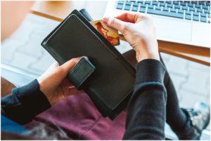 Hand zieht Geld aus einem Portemonnaie