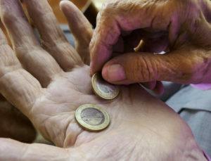 ältere Hände halten einen Euro