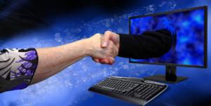 Hand aus dem Monitor drückt eine andere Hand
