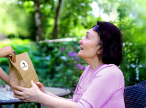 eine Dame empfängt ein Päckchen
