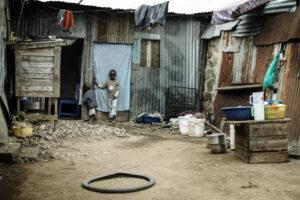 kleiner Junge steht an der Tür einer provisrischen Hütte