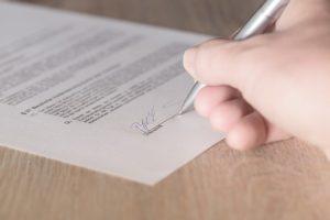 Hand unterschreibt einen Vertrag