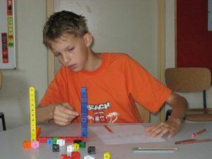 ein Junge sitzt vor Steckwürfeln