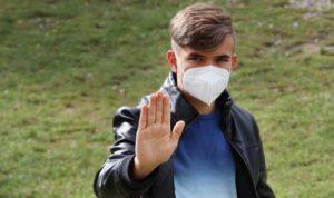 Junger Mann mit Maske und Abwehrhaltung