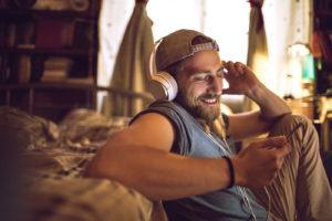 Mann sitzt mit Kopfhörern vor Sofa
