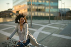 Frau faehrt Fahrrad und hoert Musik