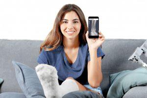 junge Frau mit Gipsfuß hält Ihr Handy mit dem Röntgenbild hoch