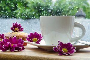 eine Kaffeetasse vor verregneter Scheibe